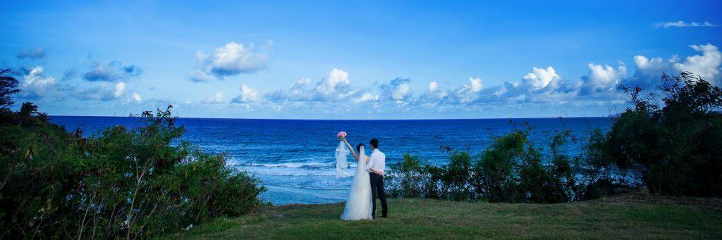 ウェディング 青い海に向かいブーケを掲げる花嫁。大自然を感じるリゾートウェディング