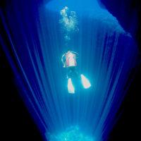 暗い洞窟の中、天井から差し込む一筋の光が、マリアナの真っ青な海をより一層引き立てます。