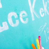 チネンアイスキャンディーストアのミントグリーンの壁の前で記念撮影